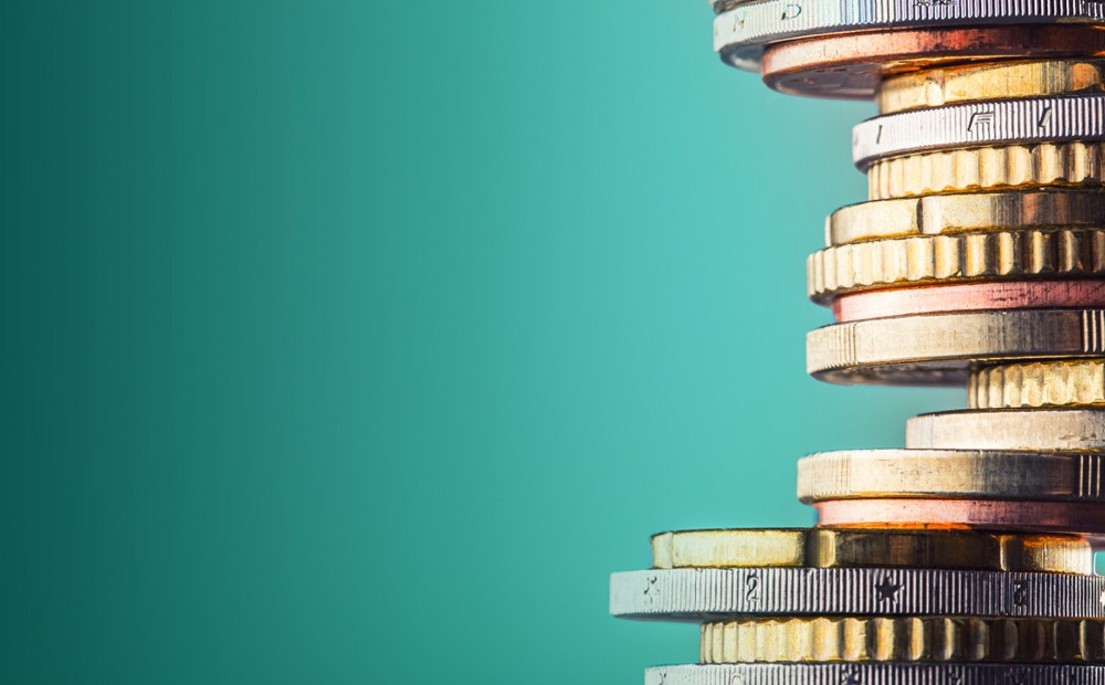 Image of stacked coins on a teal background