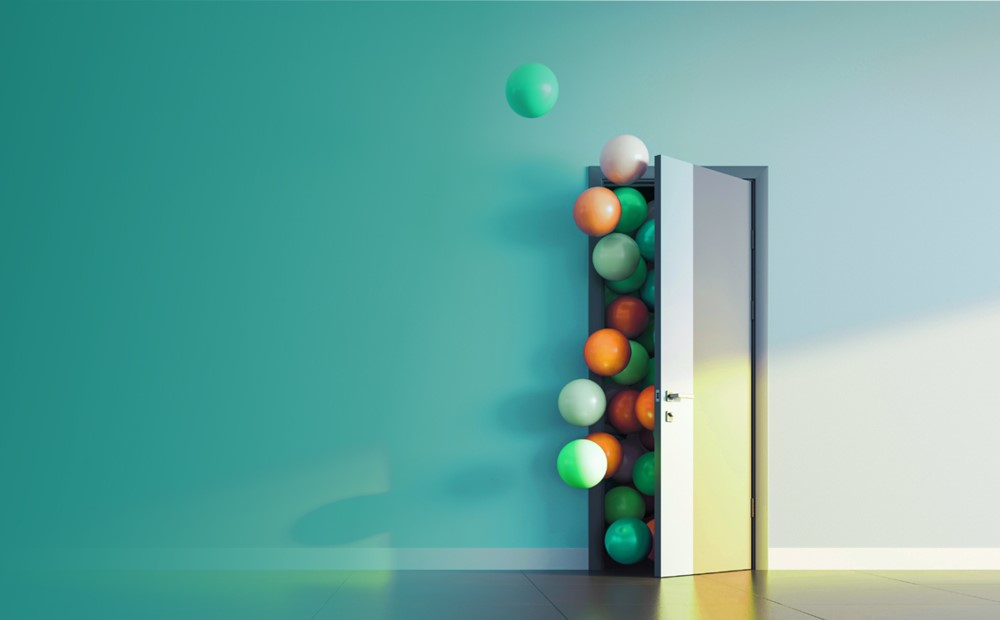 Image of a door with balloons coming out with a teal background